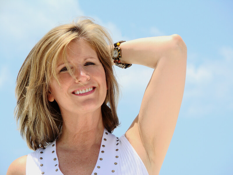 Relaxed middle-aged woman in white tank top